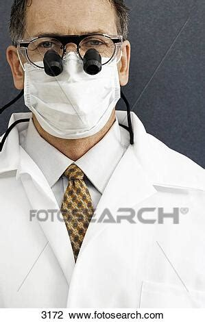 Male dentist wearing surgical mask and surgical loupes